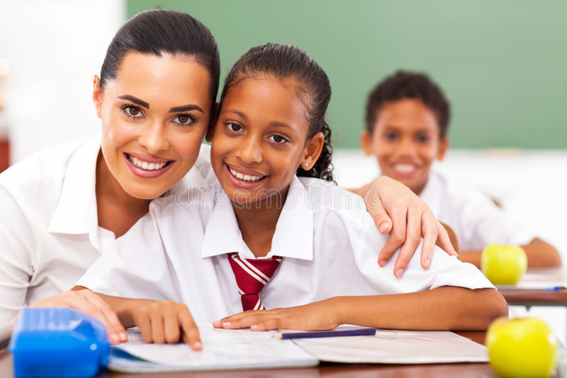 Educator and students. Pretty elementary school educator and students in classroom stock images