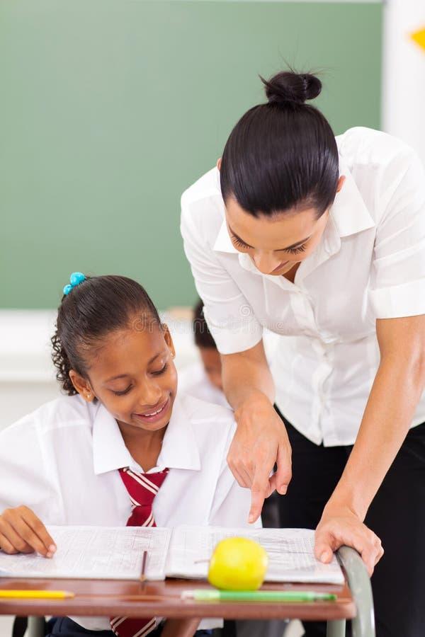 Educator tutoring student. Beautiful female primary educator tutoring student in school royalty free stock image