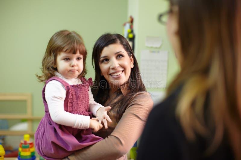 Educatore e madre con la bambina al banco immagini stock libere da diritti
