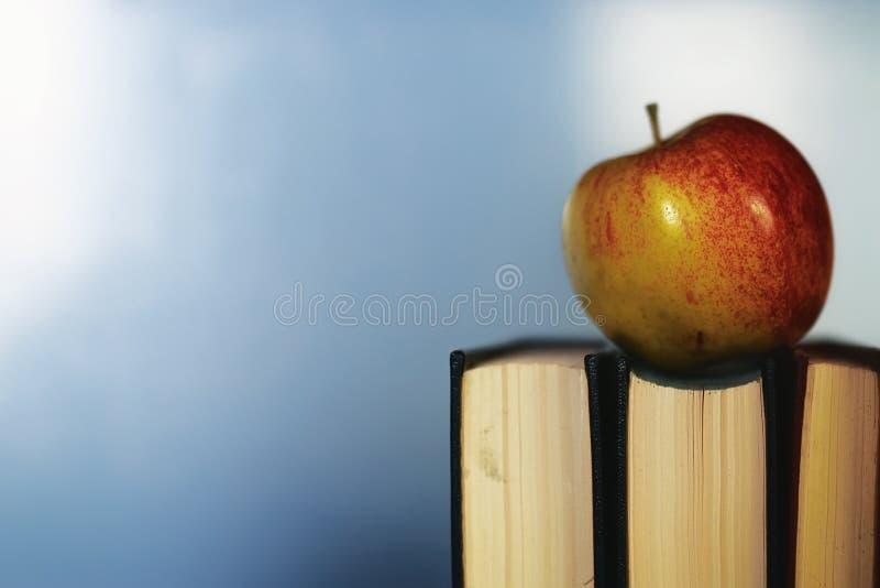 Edukaci pojęcia książek sterta, jabłko i pióro, zdjęcie royalty free