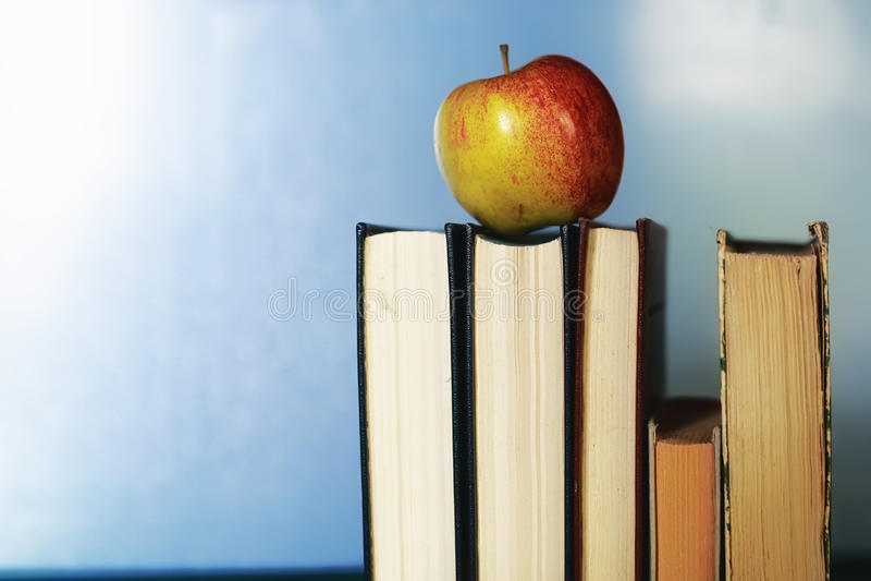Edukaci pojęcia książek sterta, jabłko i pióro, obraz royalty free