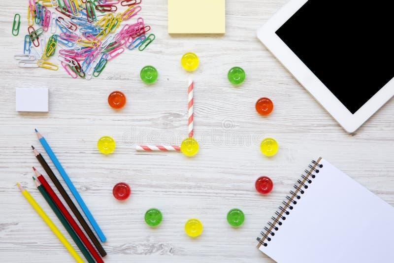Edukaci pojęcie szkoła, z powrotem Dziewięć godzin na zegarku Zegar robić kolorowi słodcy cukierki, akcesoria dla nauki nad biele zdjęcia stock