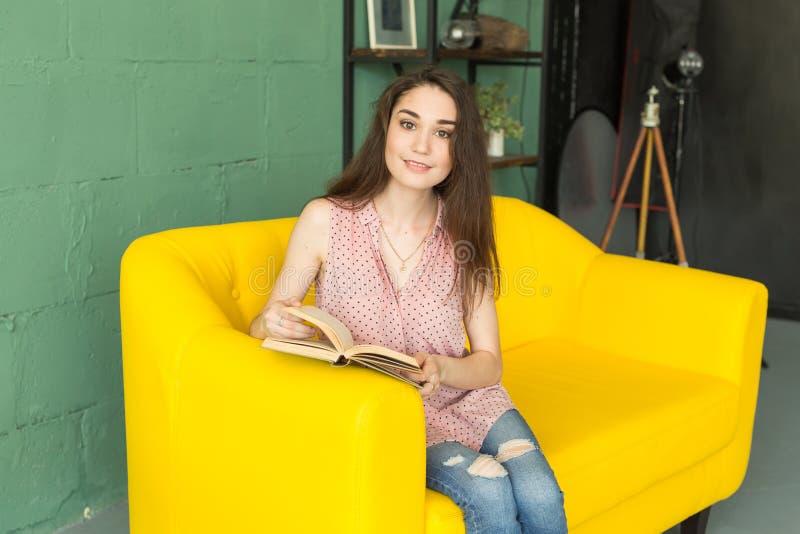 Edukacja i ludzie pojęć - młodej kobiety obsiadanie na żółtej leżance z książką zdjęcia royalty free