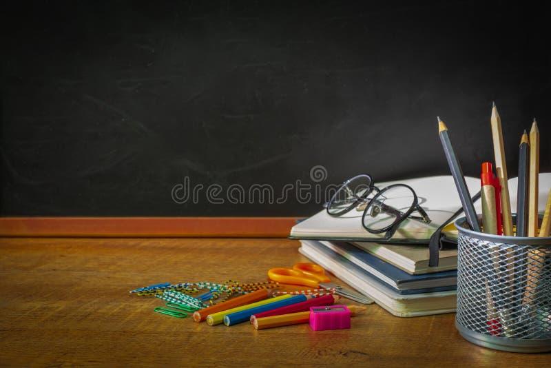 Edukacja, pojęcie Z powrotem szkoła frontowy widok Szkolnych dostaw chalkboard na drewnianym stole z książkami, szkła, kolor, ołó zdjęcie royalty free