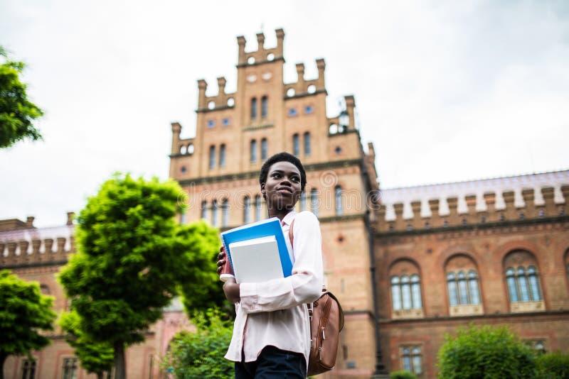 Edukacja, technologia i ludzie pojęć, Uśmiechnięty żeński amerykanin afrykańskiego pochodzenia uczeń z torbą i bierze oddaloną fi zdjęcia royalty free