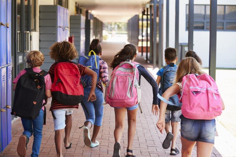 Eduque as crianças que correm no corredor da escola primária, vista traseira fotos de stock royalty free