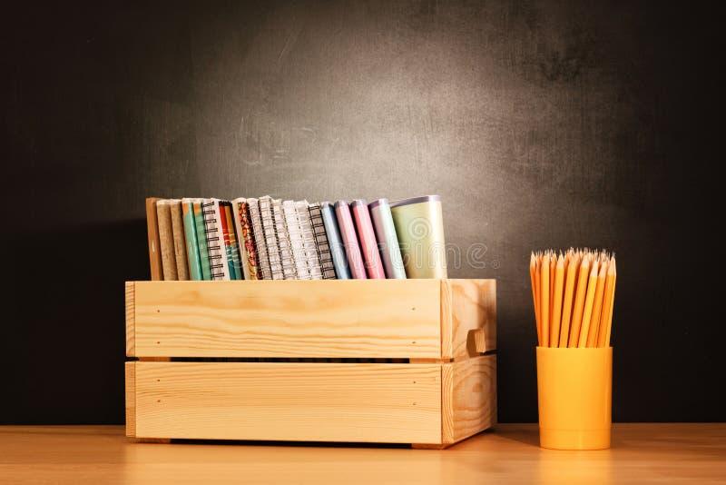 Eduque cadernos em seguido em uma caixa de madeira e em lápis em uma mesa de madeira da escola na frente de um quadro preto Conce fotografia de stock royalty free