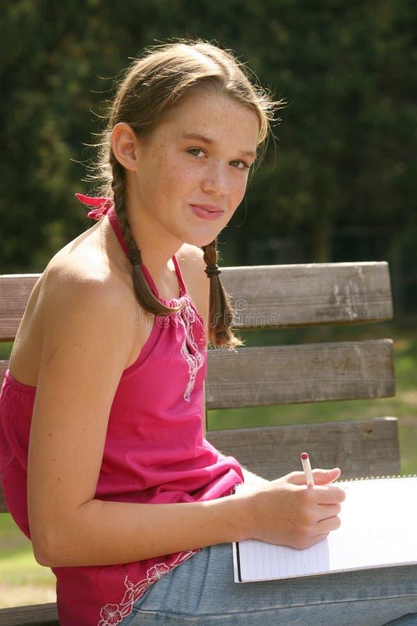 Eduque a escrita da menina no caderno ao ar livre imagens de stock royalty free