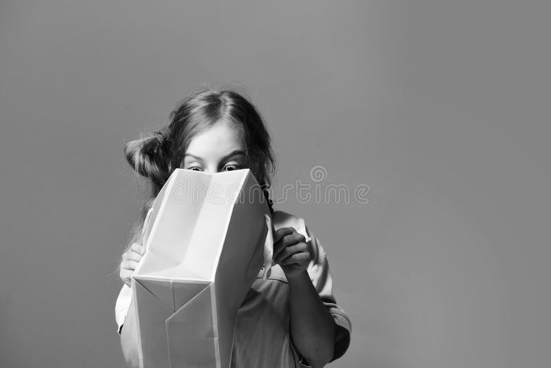 Eduque a menina com o pacote isolado no fundo vermelho salmon imagem de stock