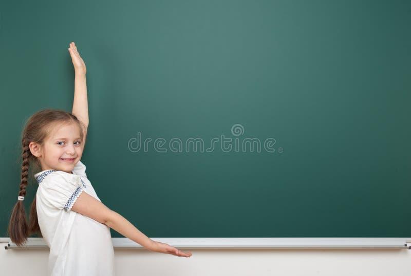 Eduque a menina do estudante que levanta no quadro-negro, em fazer caretas e nas emoções limpos, vestidos em um terno preto, conc imagem de stock