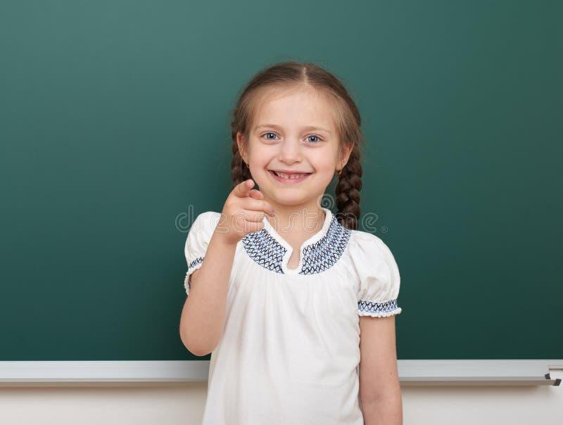 Eduque a menina do estudante que levanta no quadro-negro, em fazer caretas e nas emoções limpos, vestidos em um terno preto, conc imagem de stock royalty free