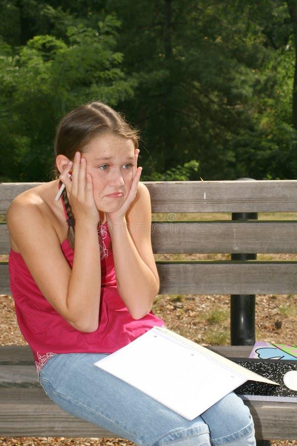 Eduque a menina que trabalha em trabalhos de casa difíceis imagens de stock