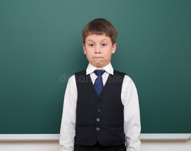Eduque o menino do estudante que levanta e pense no quadro-negro, em fazer caretas e nas emoções limpos, vestidos em um terno pre fotos de stock