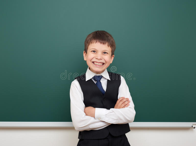 Eduque o menino do estudante que levanta no quadro-negro, em fazer caretas e nas emoções limpos, vestidos em um terno preto, conc imagens de stock
