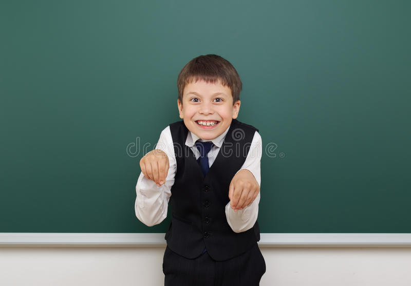 Eduque o menino do estudante que levanta no quadro-negro, em fazer caretas e nas emoções limpos, vestidos em um terno preto, conc imagens de stock royalty free