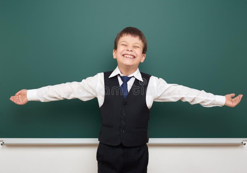 Eduque o menino do estudante que levanta no quadro-negro limpo e nos braços abertos, fazer caretas e emoções, vestidos em um tern fotos de stock royalty free