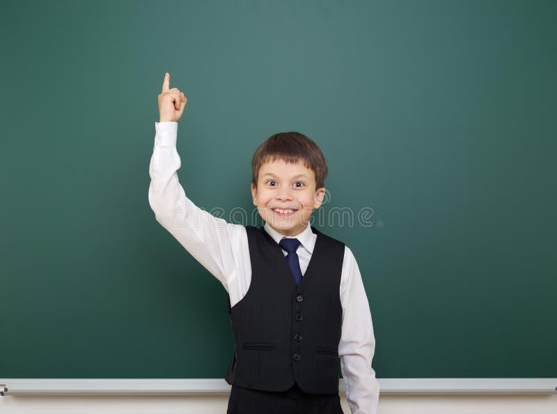 Eduque o menino do estudante que levanta no quadro-negro limpo, mostre o dedo acima e aponte, fazer caretas e emoções, vestidos e foto de stock