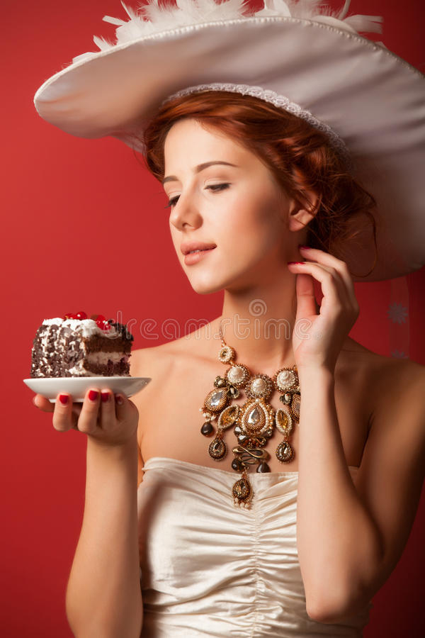 Edvardian women with cake. Portrait of redhead edvardian woman with cake on red background stock photography