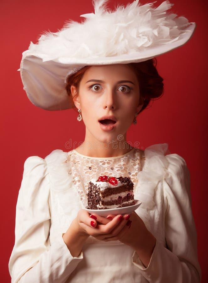 Edvardian women with cake. Portrait of redhead edvardian woman with cake on red background royalty free stock photo