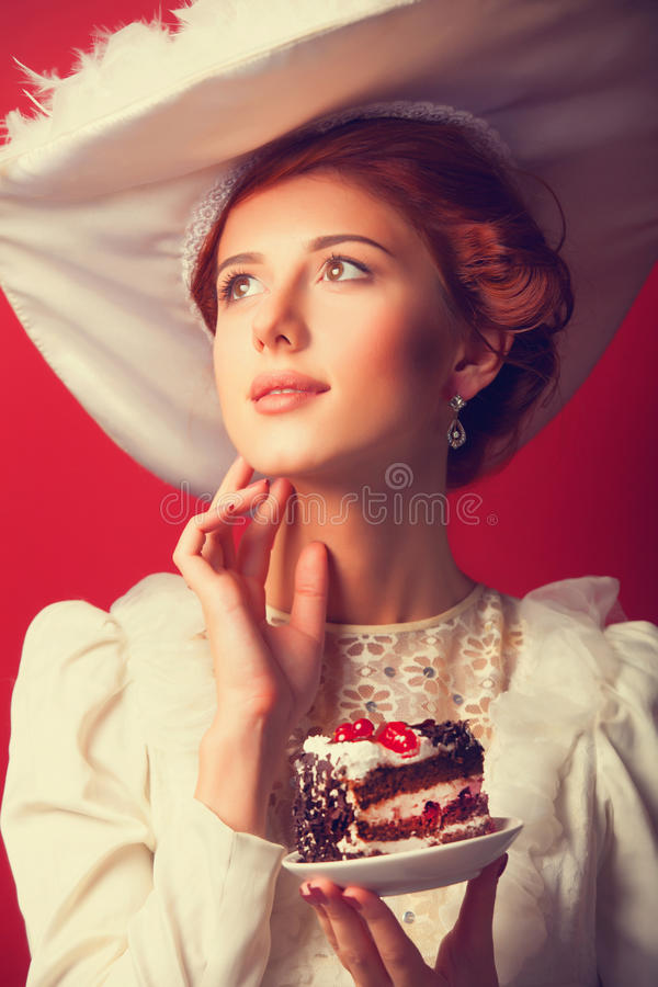 Edvardian women with cake. Portrait of redhead edvardian woman with cake on red background stock photos