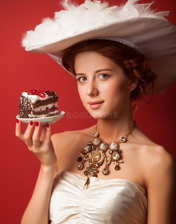 Edvardian women with cake. Portrait of redhead edvardian woman with cake on red background royalty free stock photos