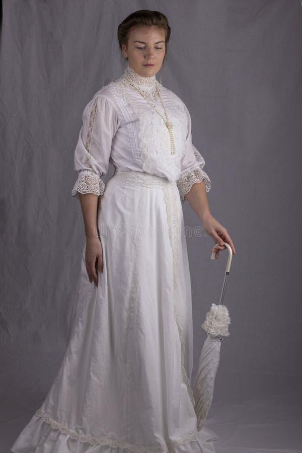 Edwardian-Frau in der weißen Blusen-, Rock- und Hutstellung gegen einen Studiohintergrund stockfotos