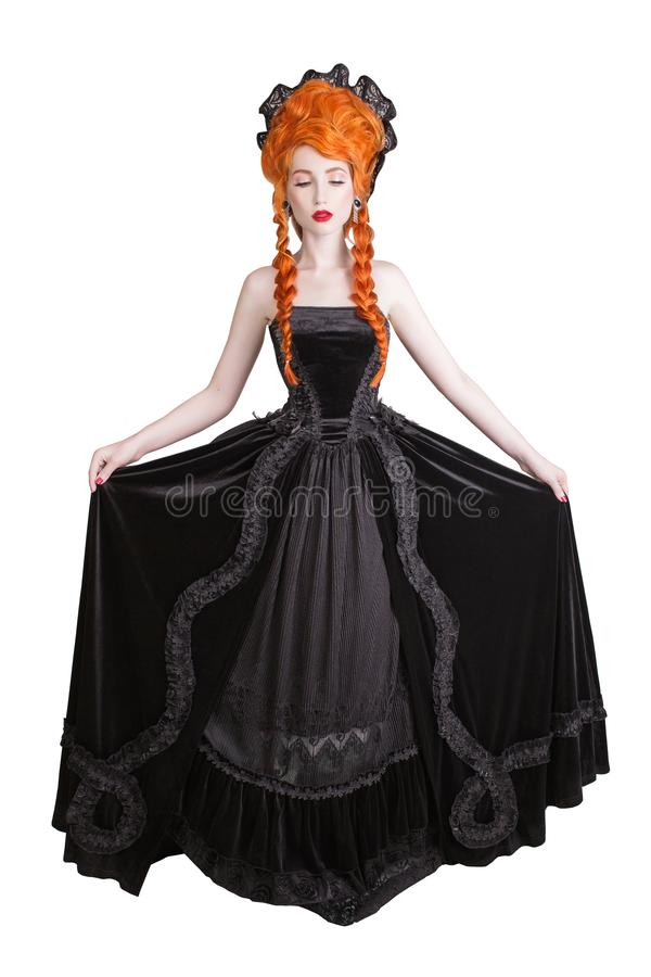 Edwardian redhead queen with halloween hairstyle isolated on white background. Fairytale queen in black gothic dress. Edwardian princess with red hair isolated stock photography