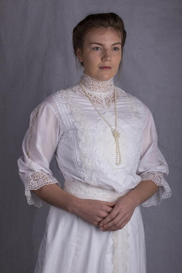 Edwardian woman in white blouse and skirt standing against a studio backdrop. Looking into distance stock photos