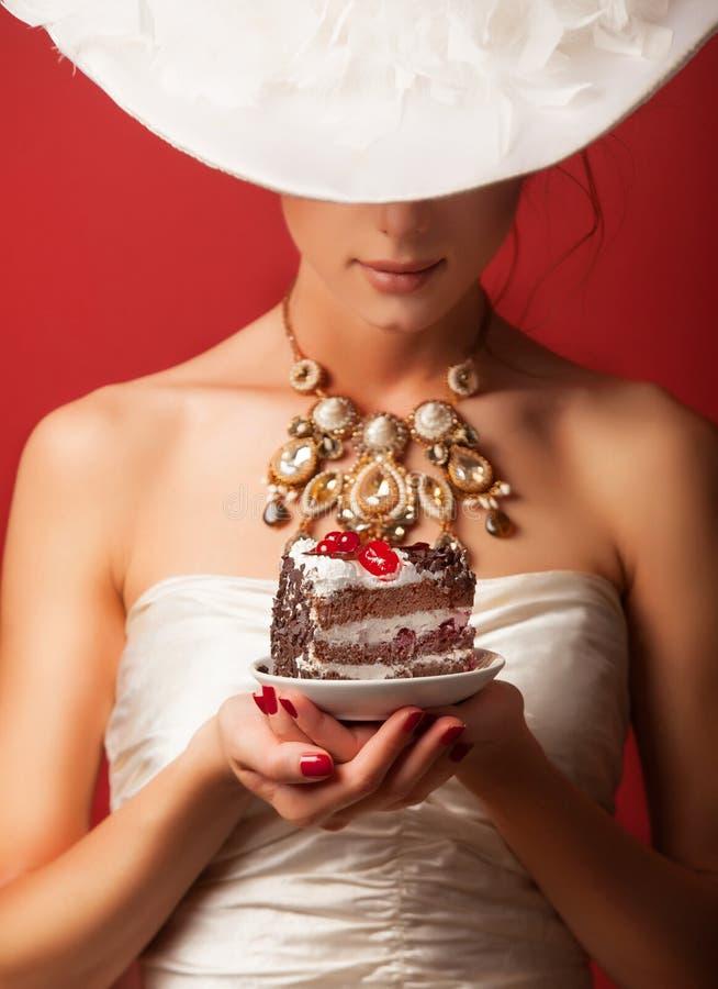 Edwardian women with cake. Portrait of redhead edwardian woman with cake on red background stock photo