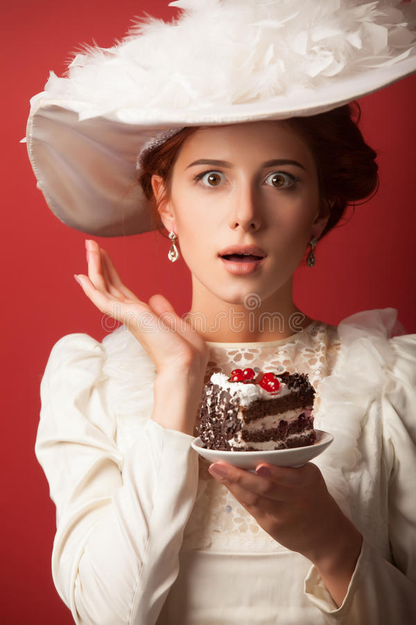 Edwardian women with cake. Portrait of redhead edwardian woman with cake on red background royalty free stock photography