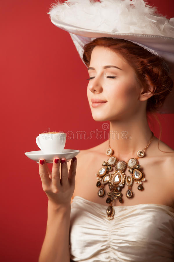 Edwardian women with cup. Portrait of redhead edwardian woman with cup on red background royalty free stock photos