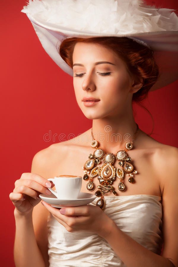 Edwardian women with cup. Portrait of redhead edwardian woman with cup on red background stock photos