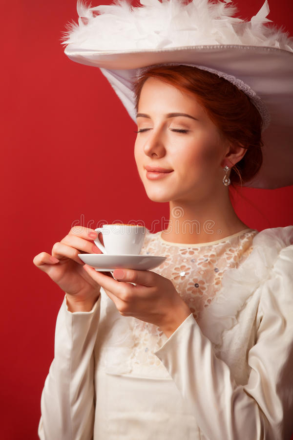 Edwardian women with cup. Portrait of redhead edwardian woman with cup on red background stock images