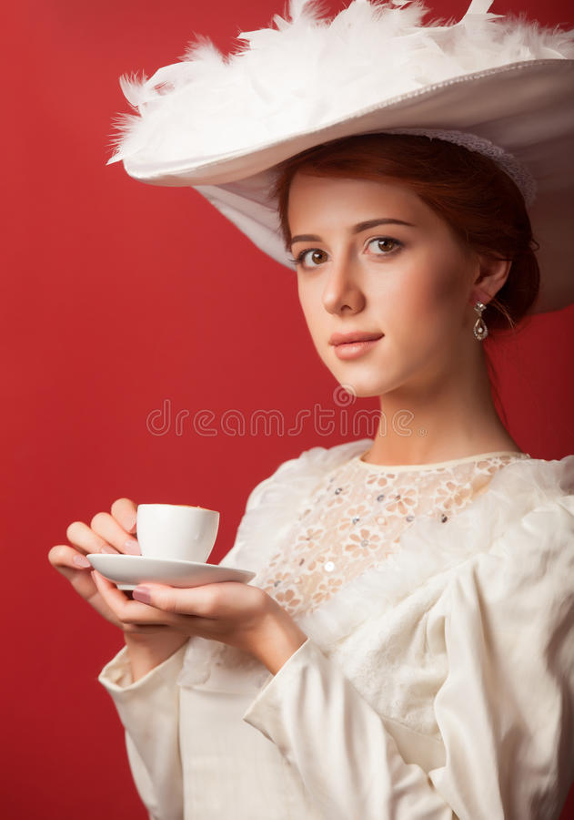 Edwardian women with cup. Portrait of redhead edwardian woman with cup on red background royalty free stock images