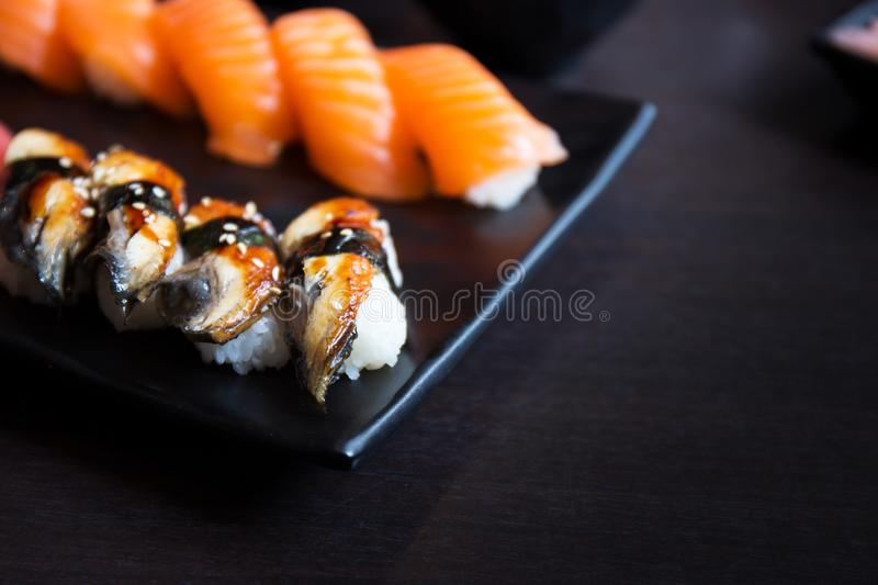 Eel and salmon sushi sashimi on black dish with empty table. Eel and salmon sushi sashimi on black dish with empty black table stock photos