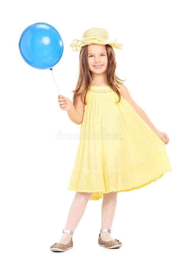 Een aanbiddelijk meisje die in gele kleding blauwe ballon houden stock afbeeldingen