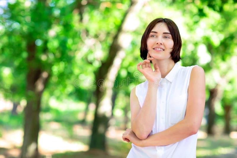Een aanbiddelijke en gelukkige dame met een kort donker kapsel op een groene achtergrond Het positieve jonge meisje Verschillende stock foto's