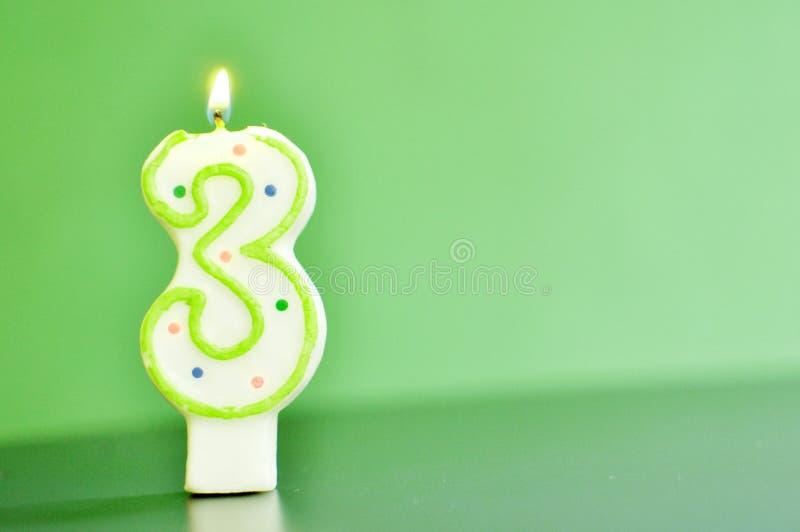 Een aangestoken kaars die cijferfiguur drie, 3, aangaande groene achtergrond met exemplaarruimte vertegenwoordigen royalty-vrije stock foto