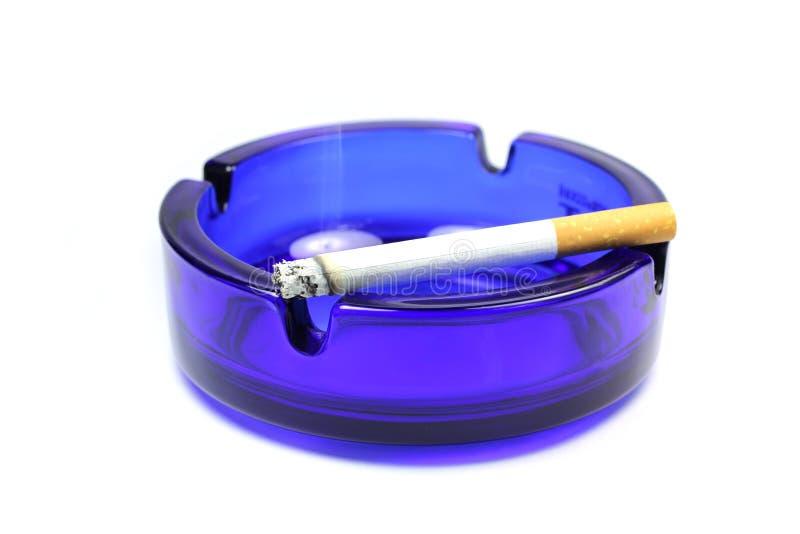 Een aangestoken sigaret in het asbakje stock foto's