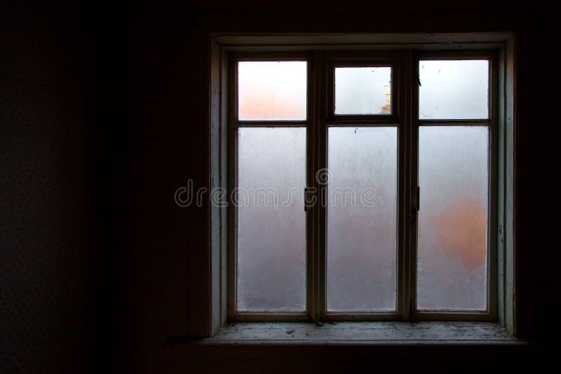 Een aangestoken venster in de zwarte ruimte van een verlaten huis, een clea stock foto
