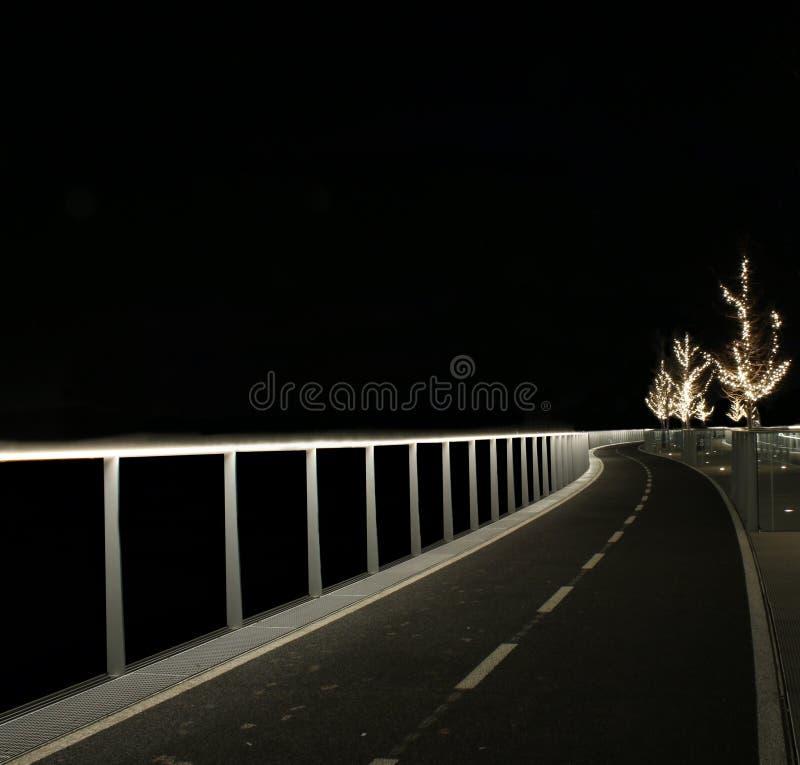 Een aangestoken weg met een paar krommen die in de duisternis leiden stock afbeelding