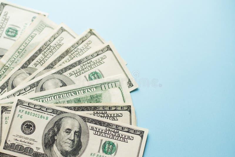 Een aantal honderd Amerikaanse dollarsnota's over lichtblauwe achtergrond Concept succes Geld stock fotografie