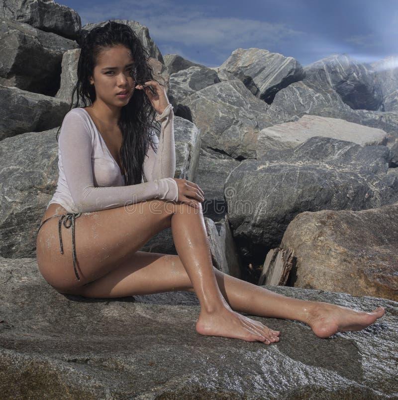 Een aantrekkelijk Aziatisch model tussen de rotsen op een zonnige dag royalty-vrije stock afbeelding