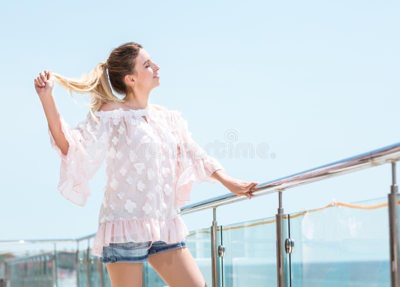 Een aantrekkelijk meisje geniet van de zomer en kijkt gelukkig Het charmeren van jong modelmeisje op een heldere blauwe hemelacht royalty-vrije stock foto's