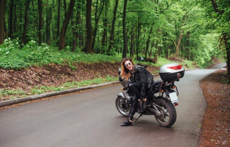 Een aantrekkelijk sexy meisje op een sportenmotor die buiten stellen stock foto's