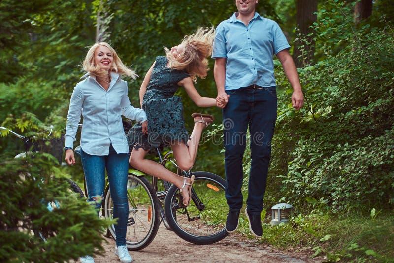 Een aantrekkelijke familie gekleed in vrijetijdskleding op een fietsrit, heeft pret en het springen in een park stock foto