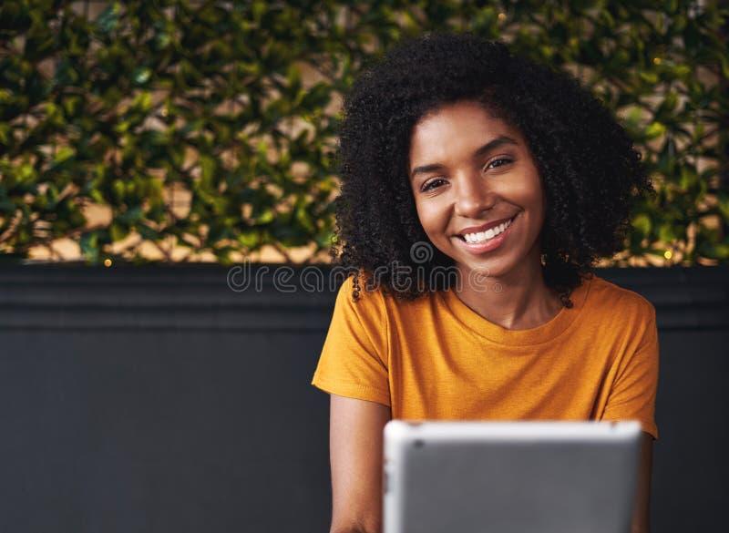 Een aantrekkelijke glimlachende jonge vrouw in koffie stock afbeeldingen