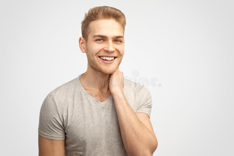 Een aantrekkelijke glimlachende leuke jonge blonde mens glimlacht merrily en bekijkt de camera close-upportret op geïsoleerde ach stock fotografie