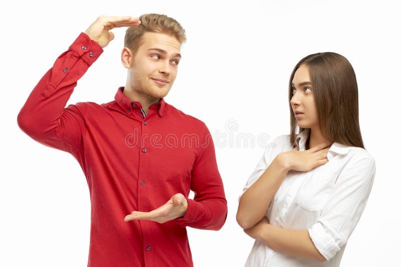 Een aantrekkelijke jonge mens in een rood overhemd, spreidt zijn handen uit, die iets tonen reusachtig aan zijn meisje stock fotografie