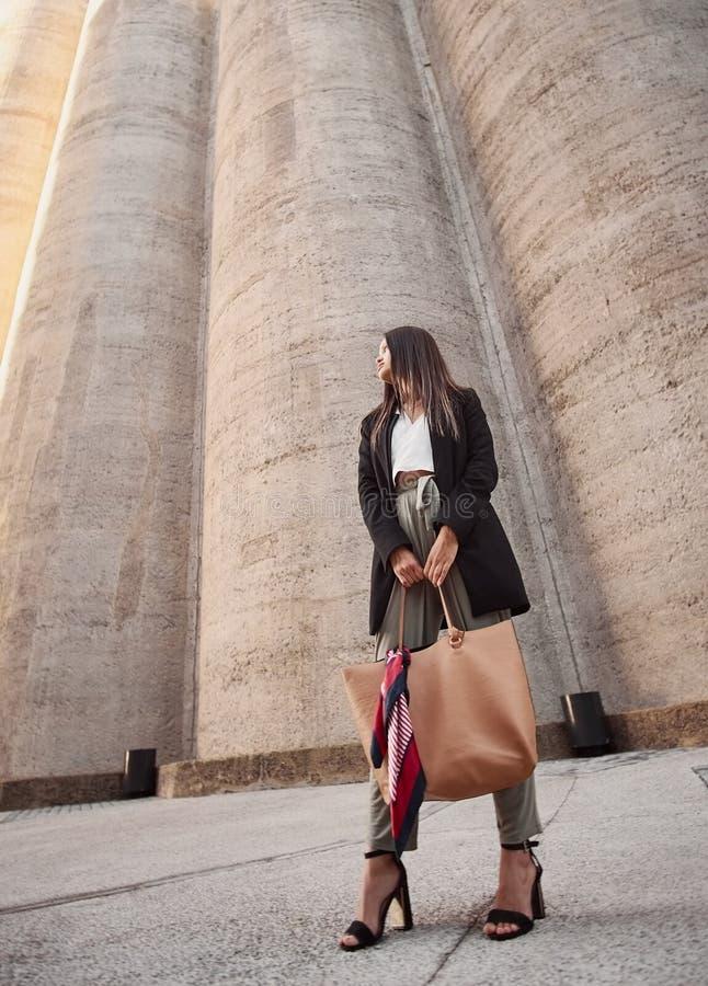 Een aantrekkelijke jonge vrouw die haar bruine handtas houden weg kijkend stock afbeeldingen